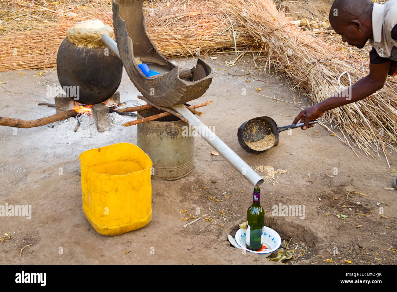 Man checks pot of cornmeal mash which will be used to make liquor in his village in Zambia, Africa. - Stock Image