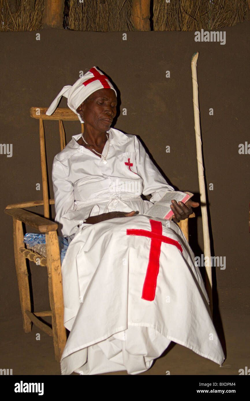 Elderly woman is native healer for village and poses in her nurse outfit. Zambia - Stock Image