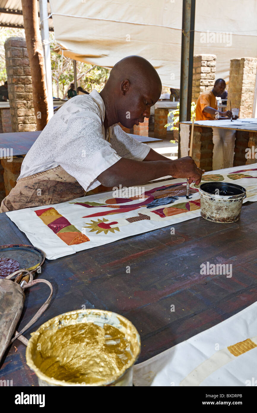 Man paints African pattern onto cloth at Tribal Textiles, a workshop in Mfuwe, Zambia. - Stock Image