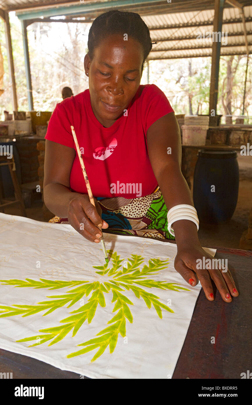Woman paints African pattern onto cloth at Tribal Textiles, a workshop in Mfuwe, Zambia. - Stock Image