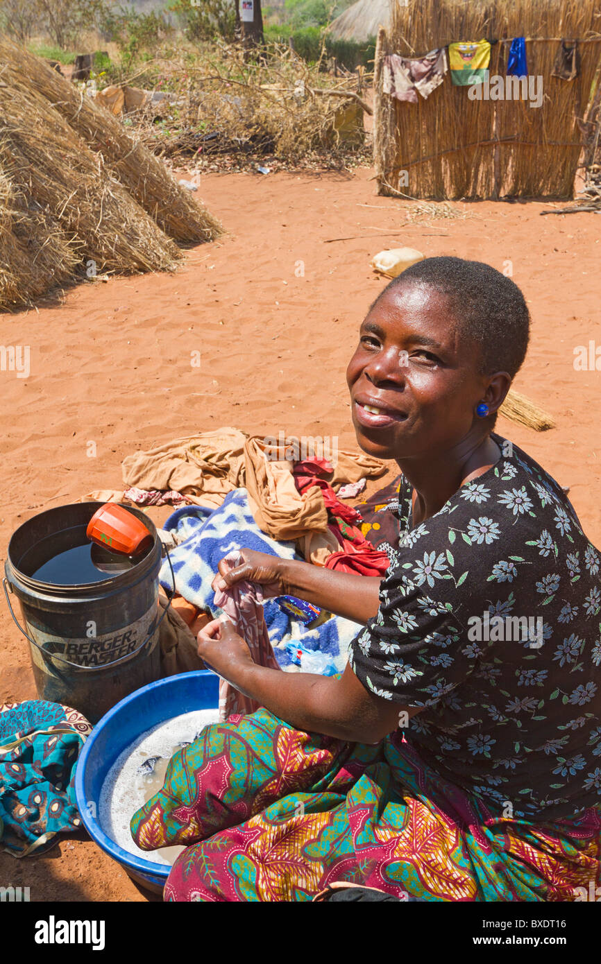 Woman washes family clothing in a pan in her village of Simoonga near Livingston, Zambia, Africa. - Stock Image