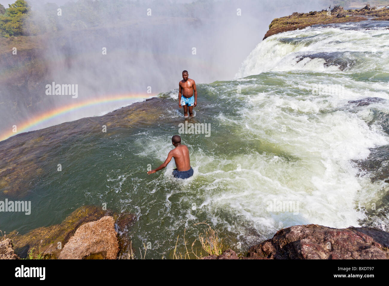 Man jumps into Devil's Pool at Victoria Falls. - Stock Image