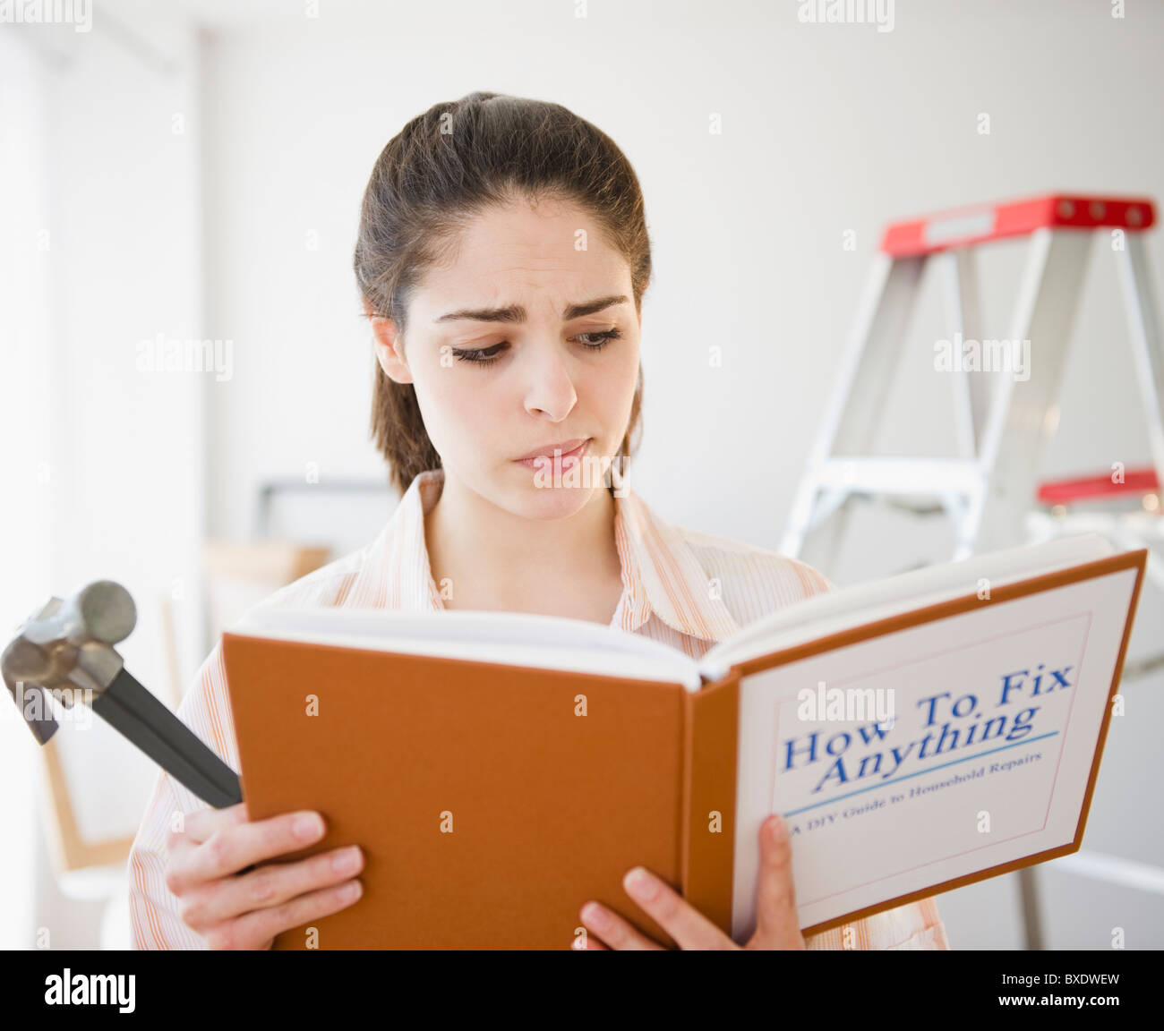 Confused woman reading do it yourself book - Stock Image