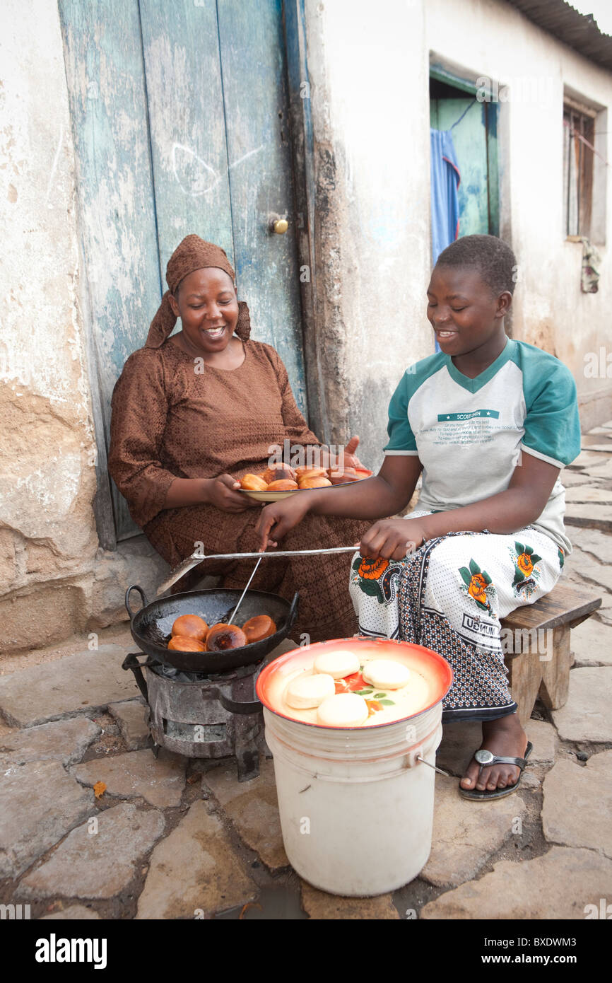 A young woman cooks mandazi (doughnuts) on the streets of Dodoma, Tanzania, East Africa. - Stock Image