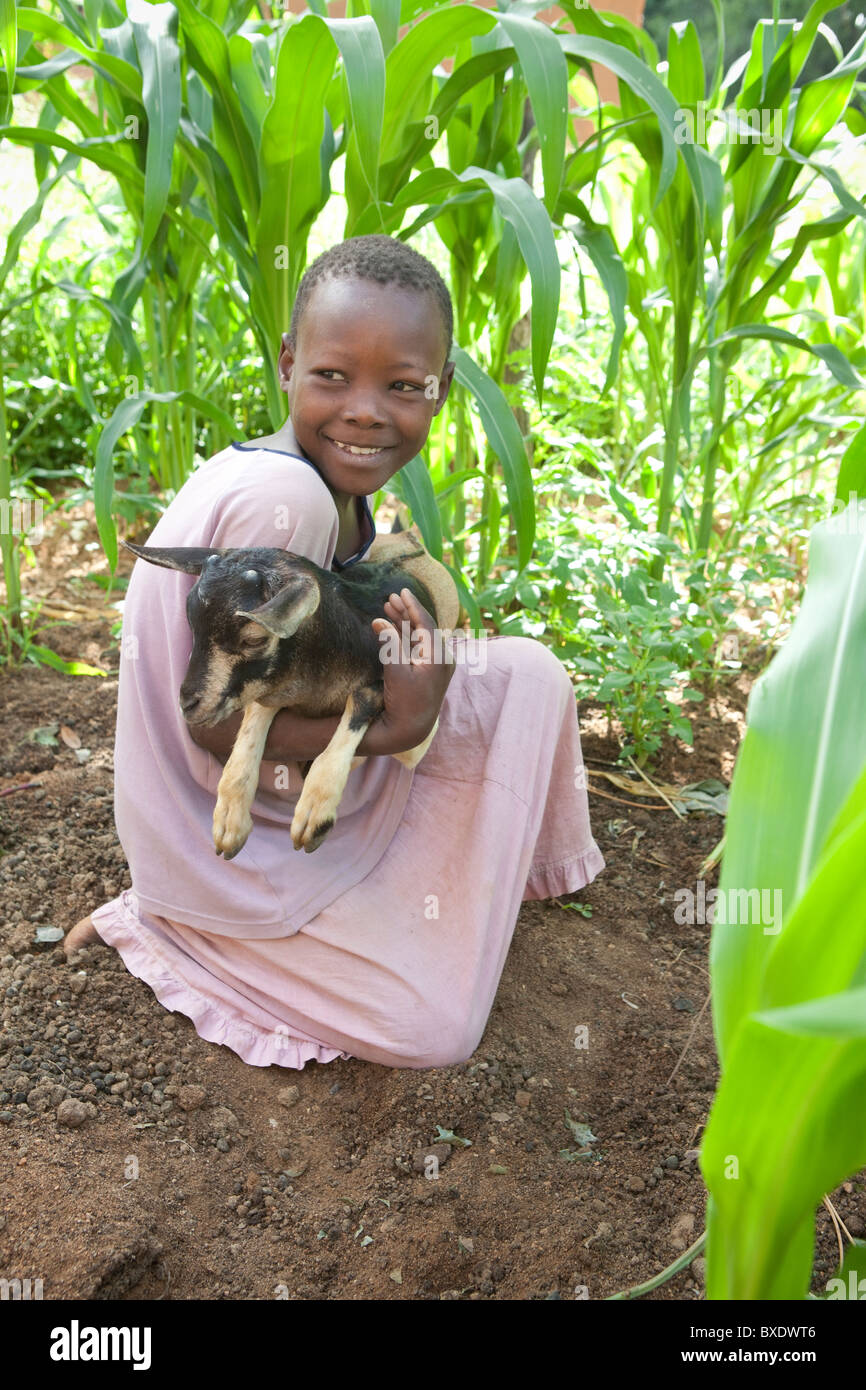 Eight year old Janet Ngasha holds a small goat in Dodoma, Tanzania, East Africa. - Stock Image
