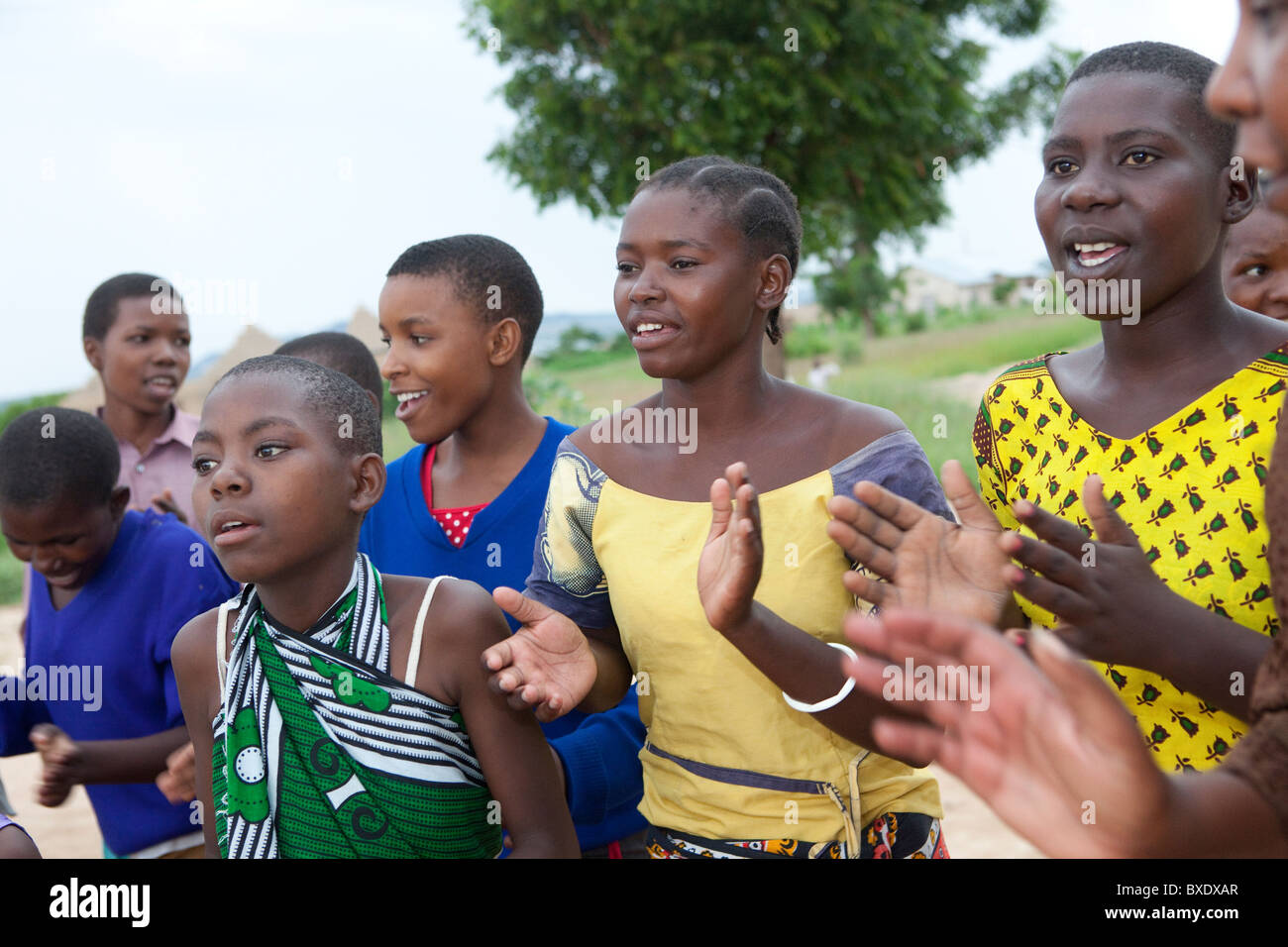 Adolescent girls sing and dance together at an after school program in Dodoma, Tanzania, East Africa. - Stock Image