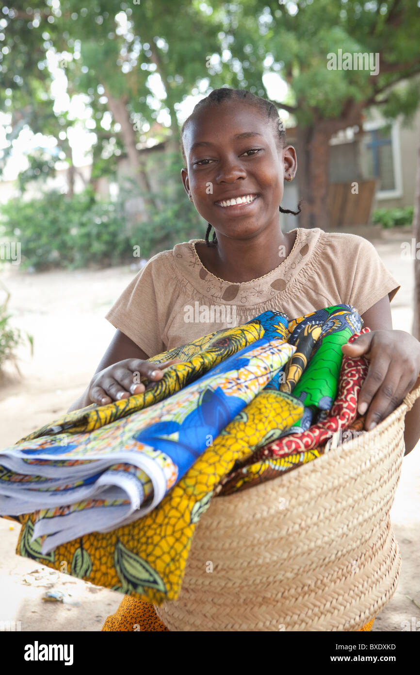 A young woman sells cloth and textiles door to door in Dodoma, Tanzania, East Africa. - Stock Image