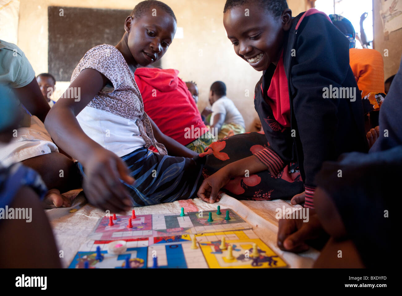 Adolescent girls play board games together at an after school program in Iringa, Tanzania, East Africa. - Stock Image