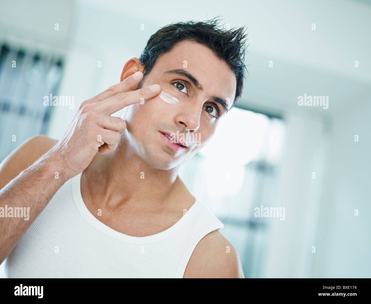 young caucasian man applying eye cream on face. Horizontal shape, front view, head and shoulders - Stock Image