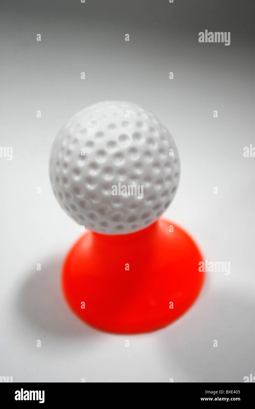 A white golf ball placed on a red peg against a white background - Stock Image