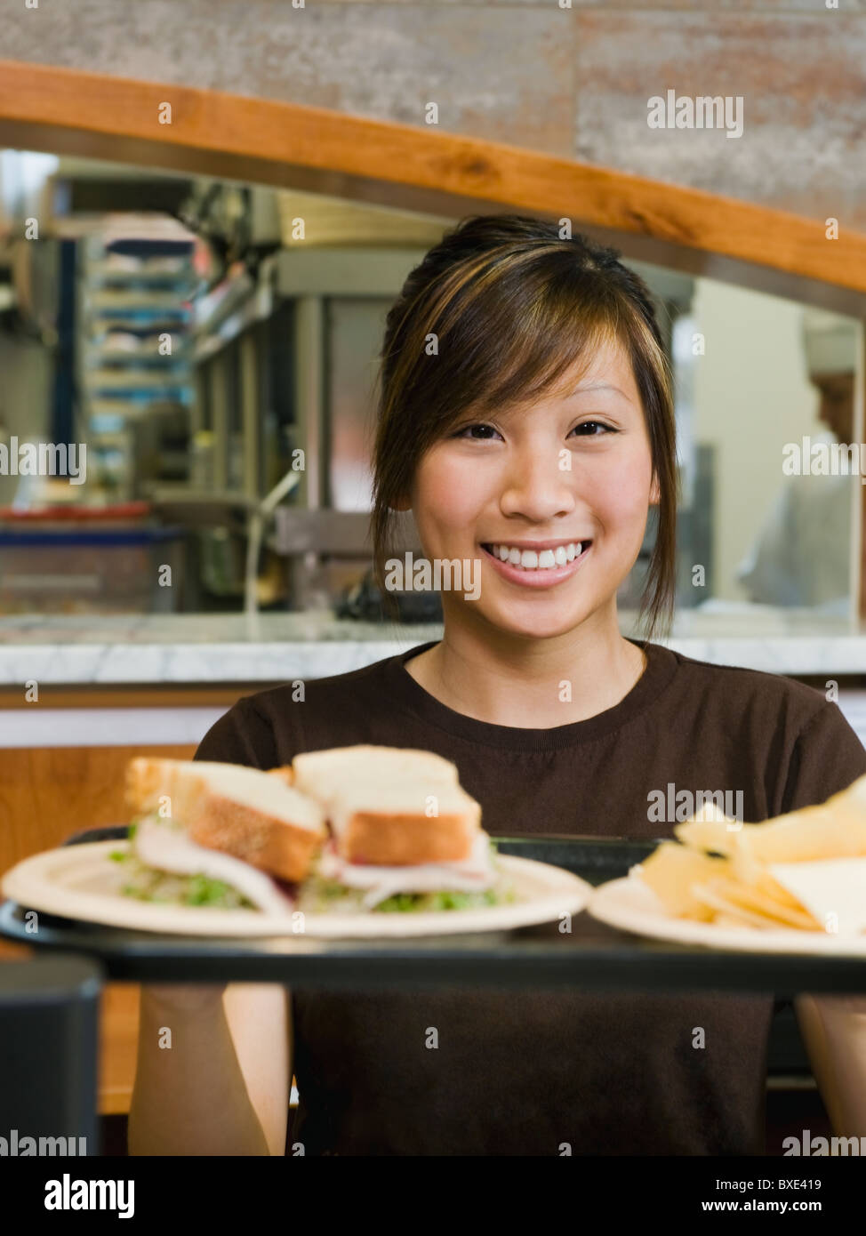 Woman holding tray of food - Stock Image