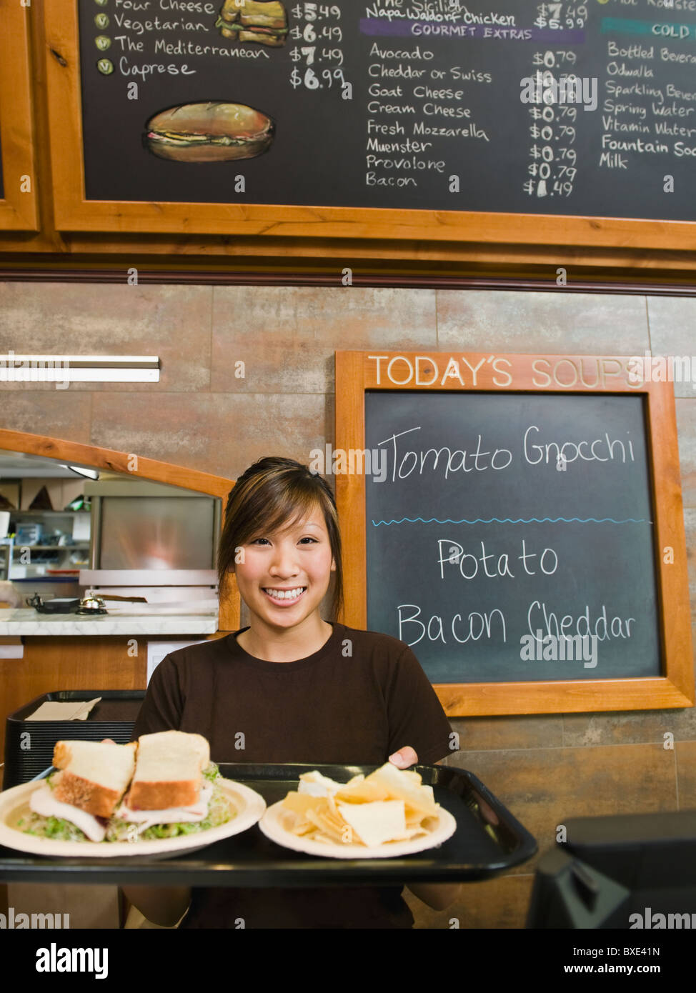 Woman holding tray of food in bakery - Stock Image