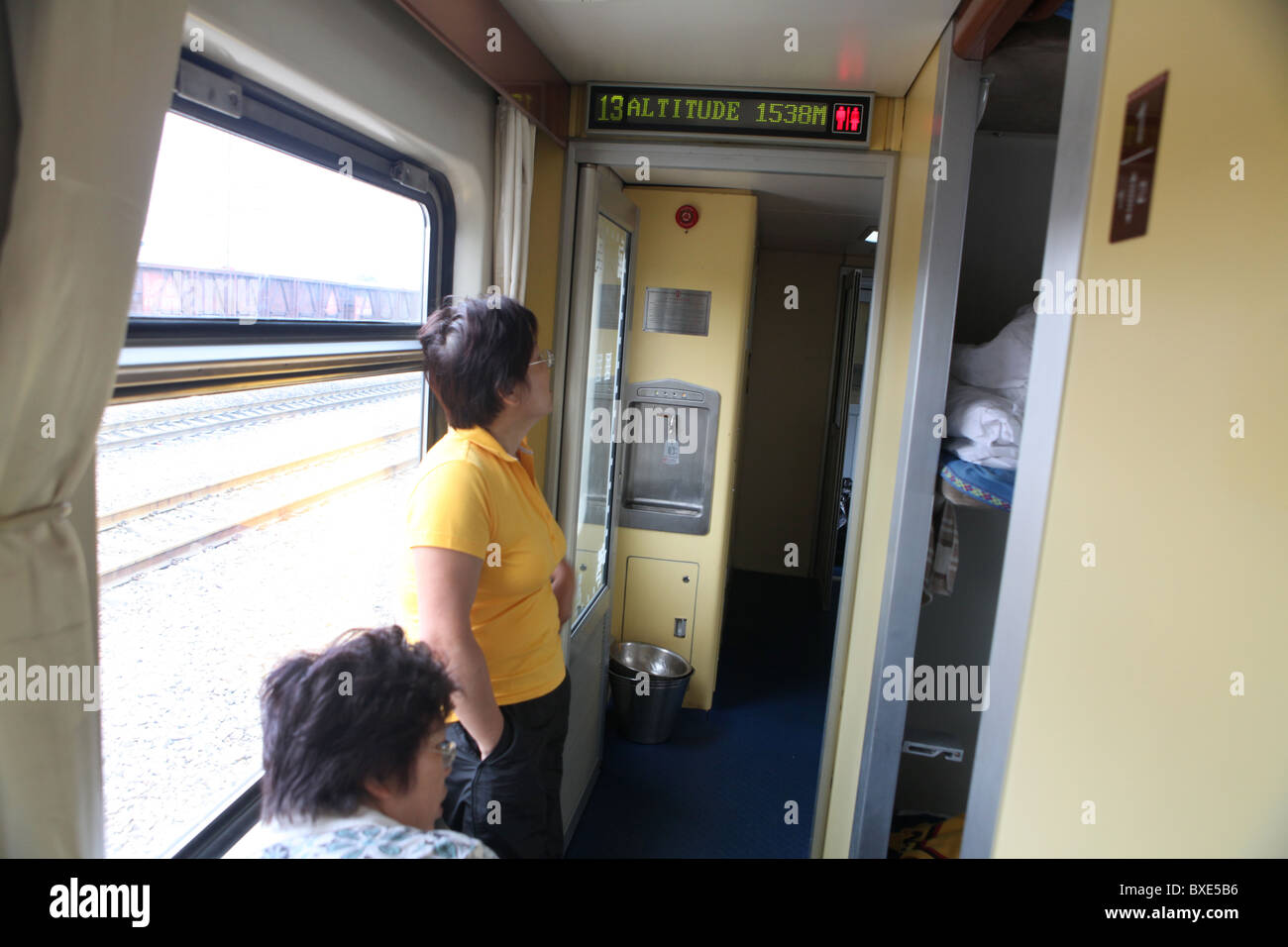 Passengers check the altitude on the Qinghai - Xizang train, the world's highest railway, here between Chengdu and Stock Photo