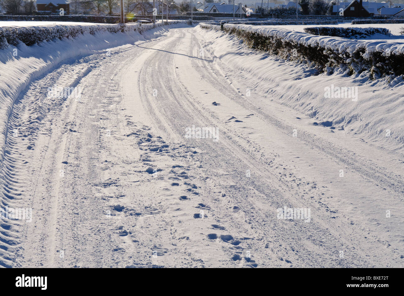 Snow covered rural road with a number of tyre tracks - Stock Image