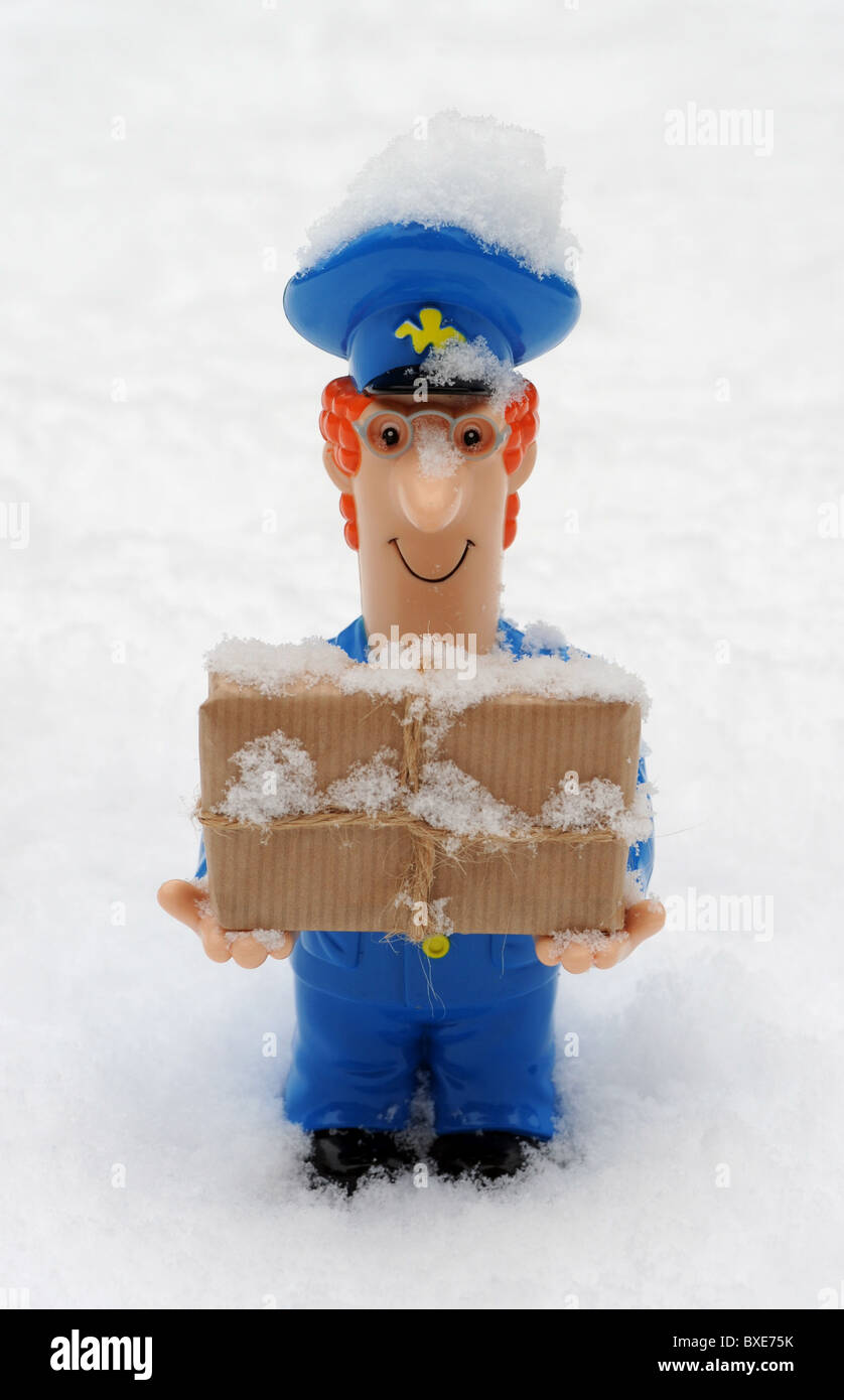 POSTMAN FIGURE WITH PARCEL IN SNOWY ICY  WEATHER CONDITIONS RE POST OFFICE WINTER DELIVERIES DELAYS ETC UK POSTAL - Stock Image