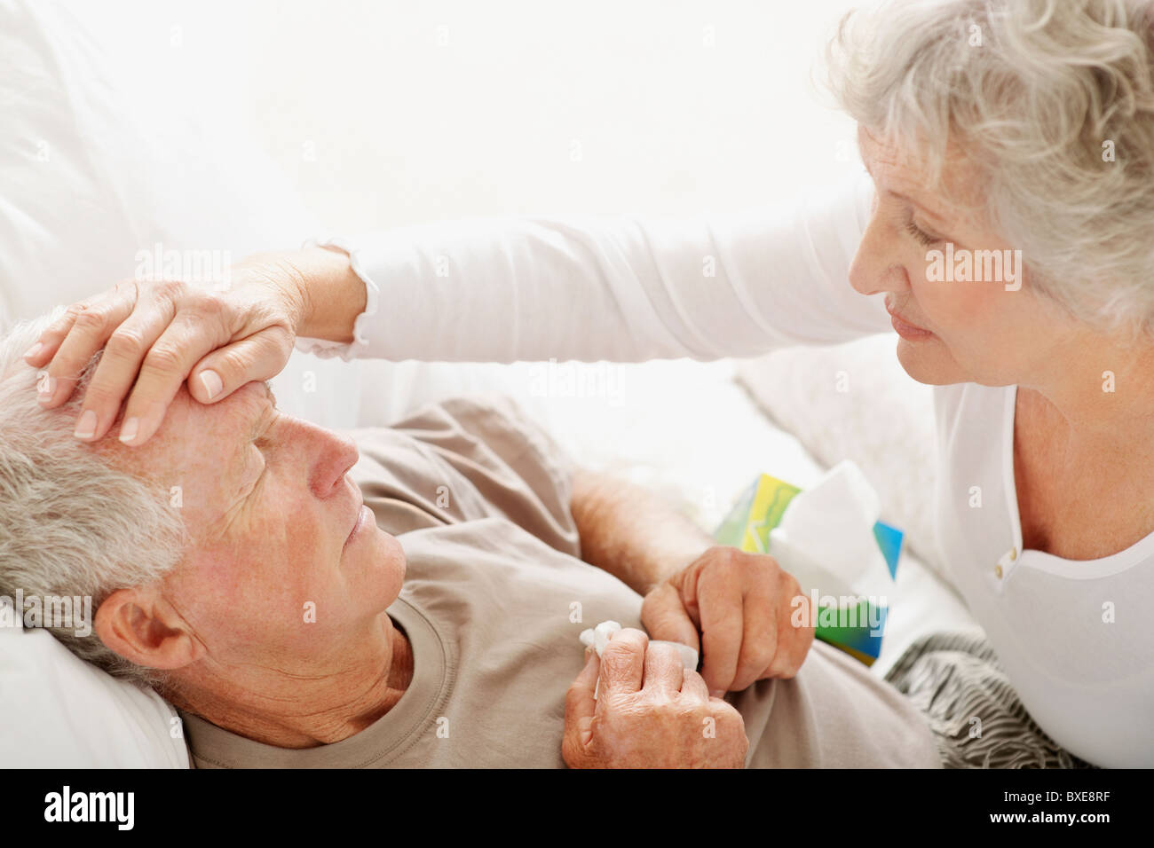 Senior woman caring for man with a fever Stock Photo