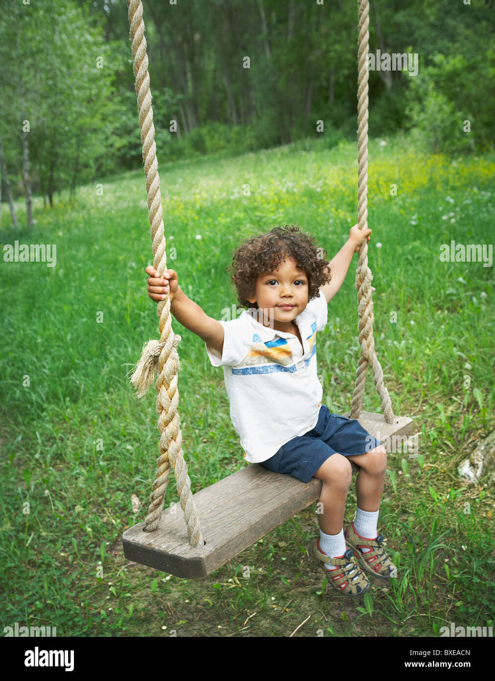 Young child sitting on large outdoor swing Stock Photo ...