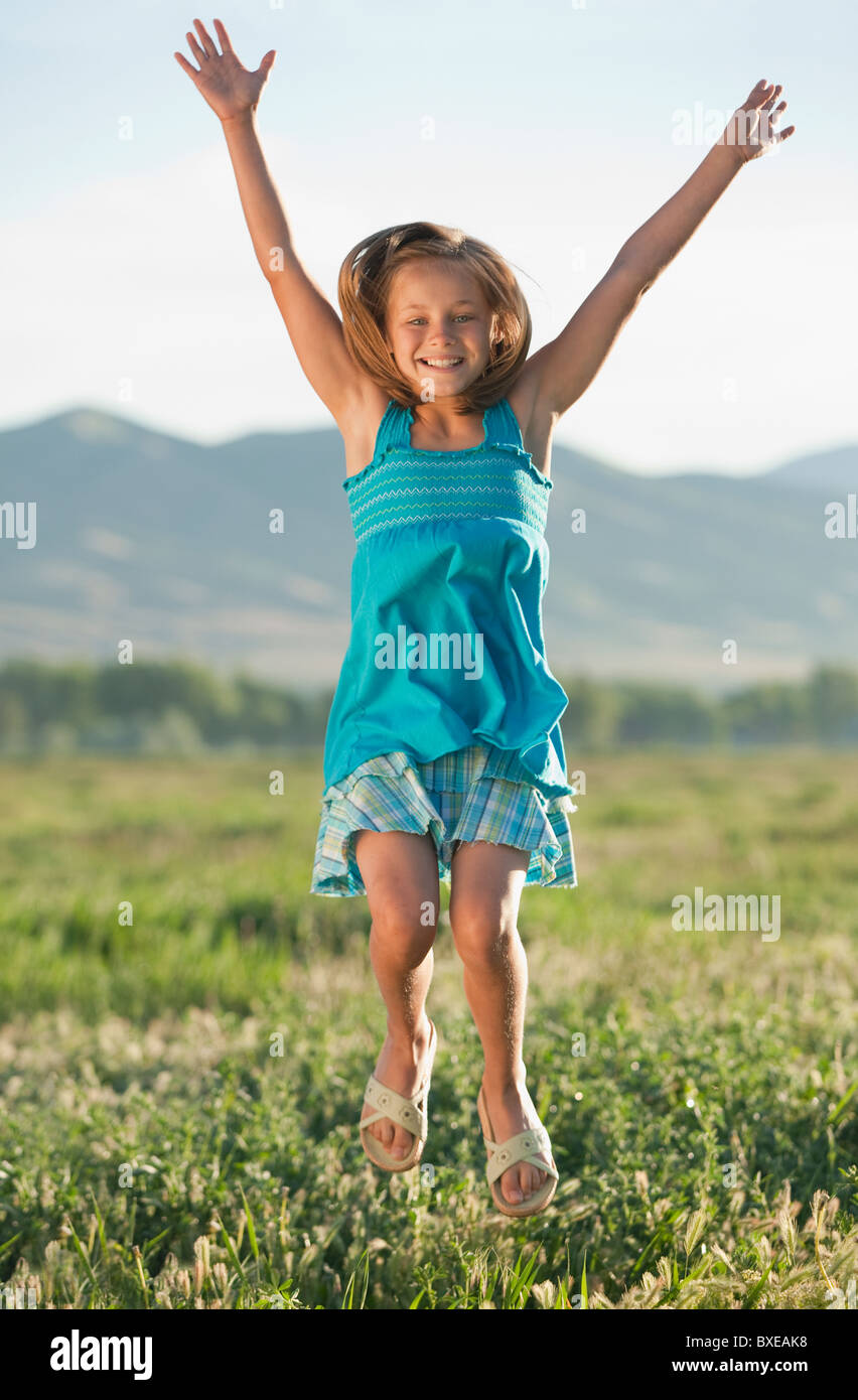 Young girl jumping in field - Stock Image