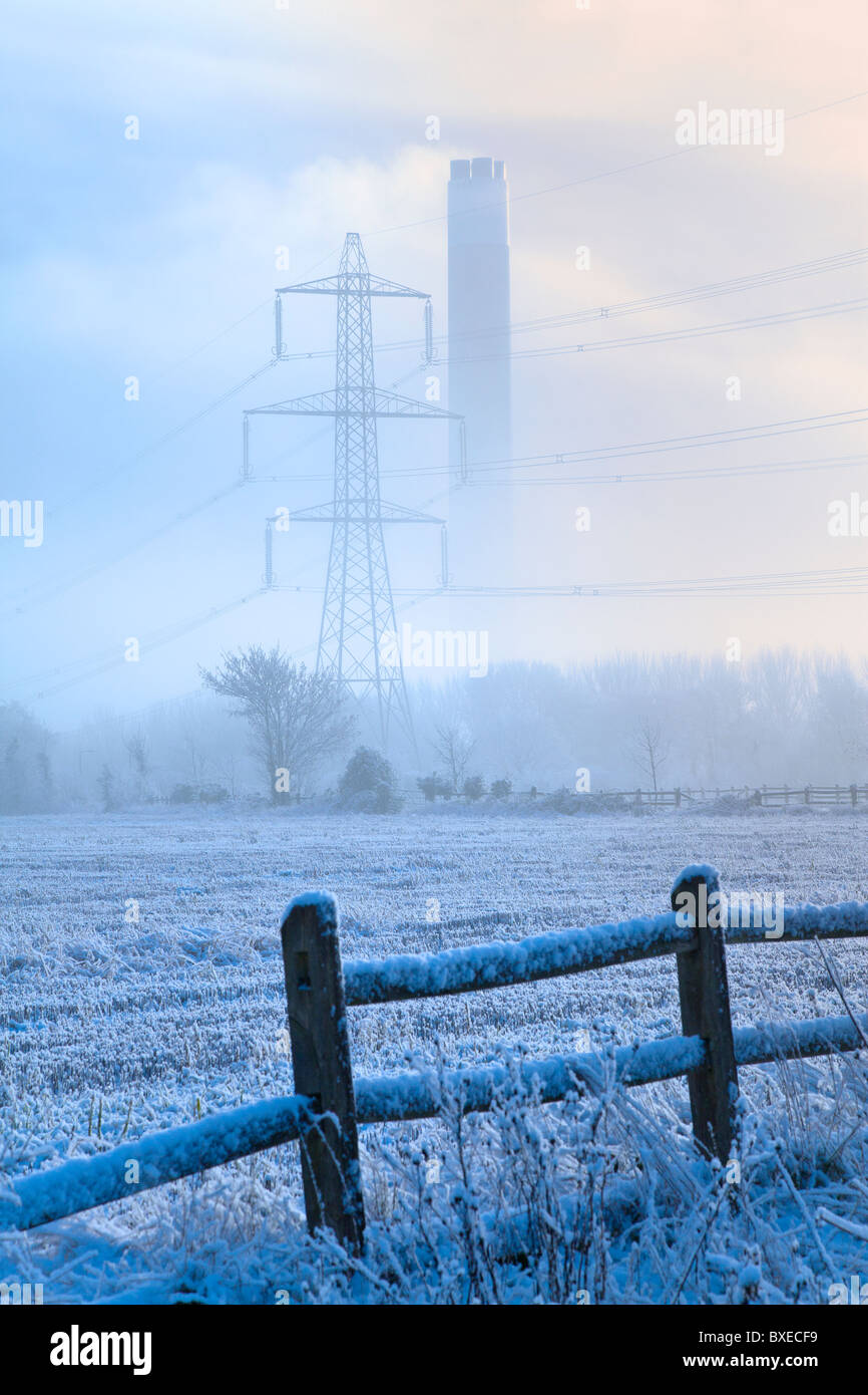 Power station chimney and electricity pylon showing through cold morning mist behind a frosty field - Stock Image