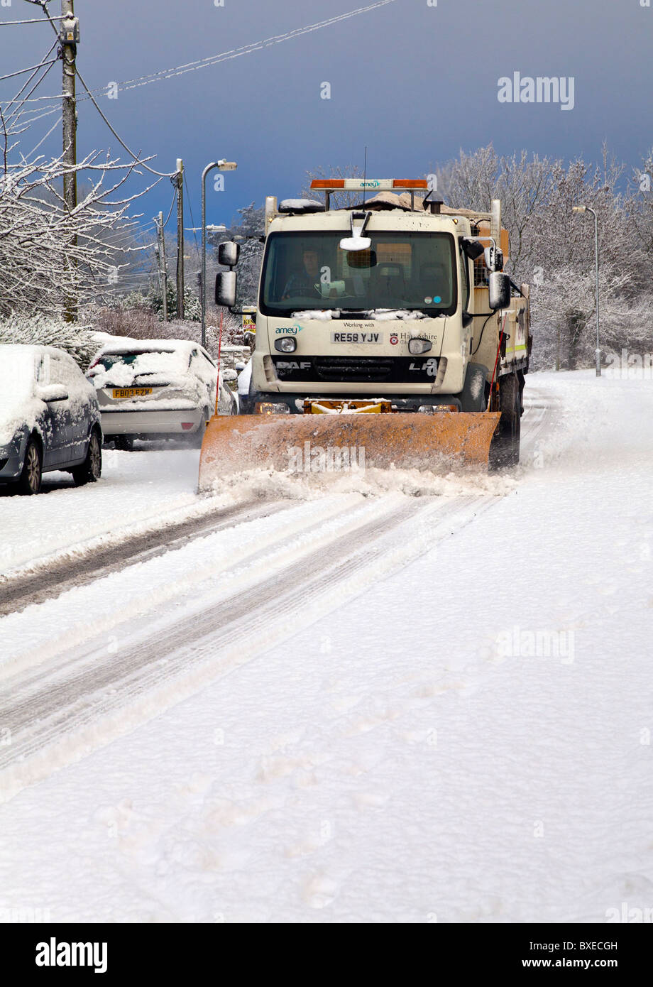 UK County Council snow plough lorry clearing snow on minor road - Stock Image