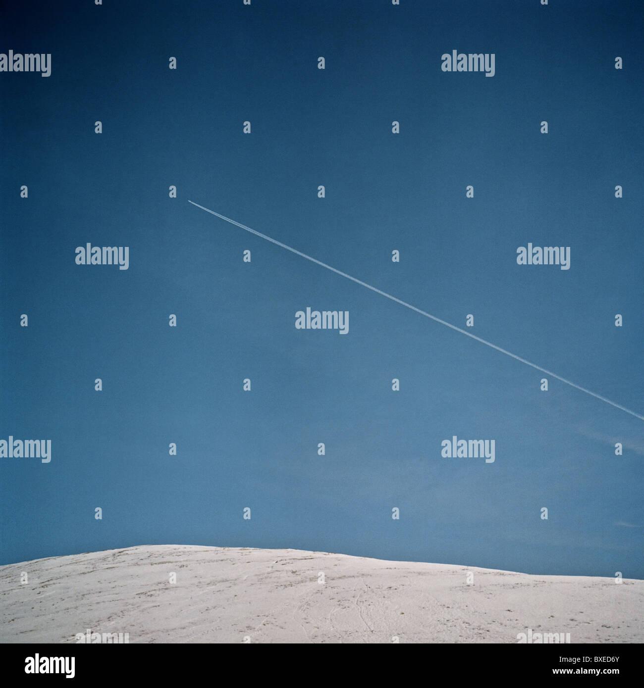 Aircraft vapor trail across blue sky. - Stock Image