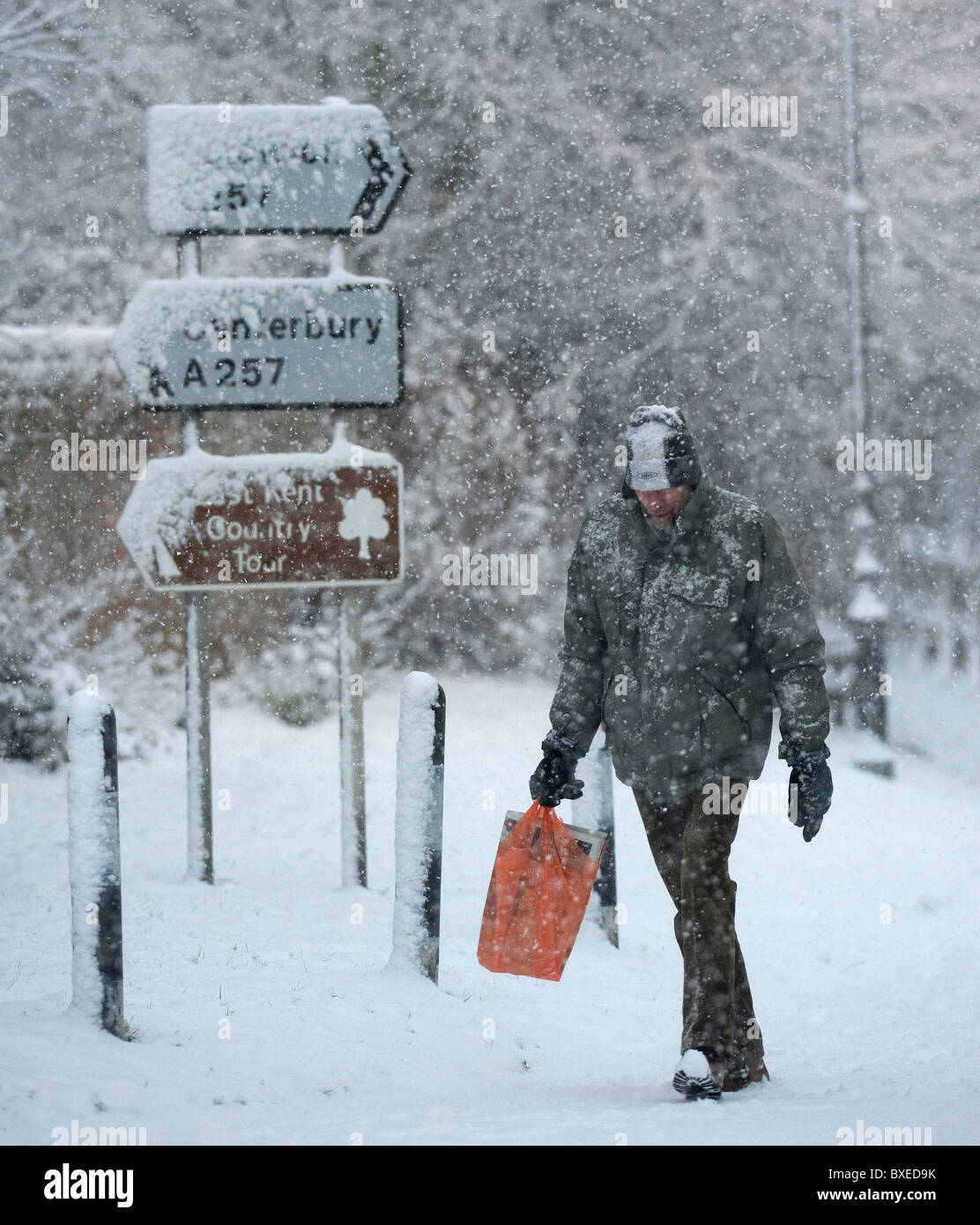 A man walks through the kent village of Wingham as the snow falls and brings chaos to the country, 18th December - Stock Image