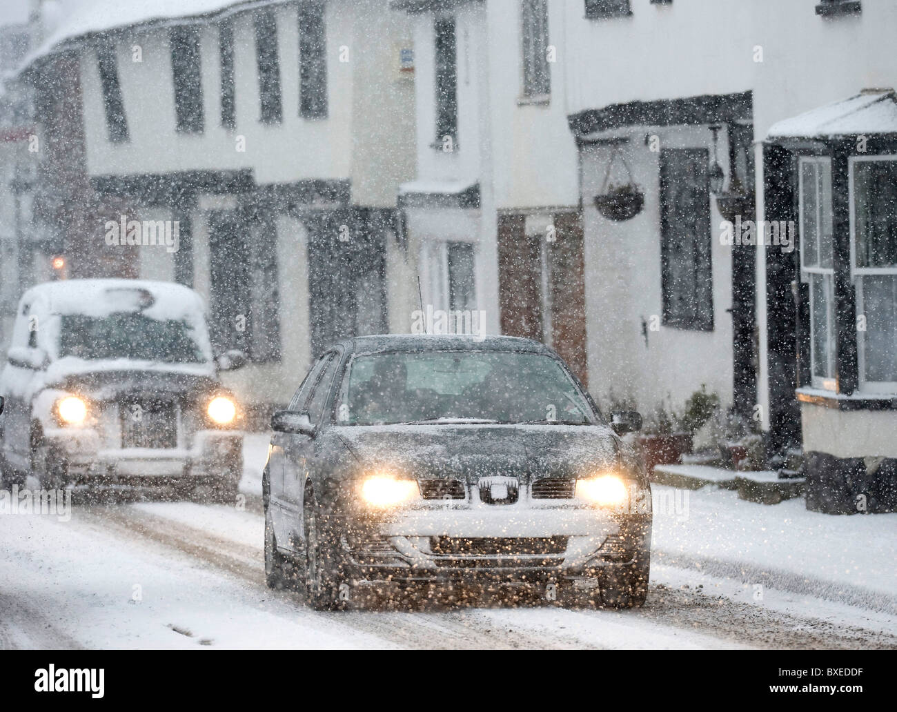 Vehicles slowly wend their way through the kent village of Wingham as the snow falls and brings chaos to the country, - Stock Image