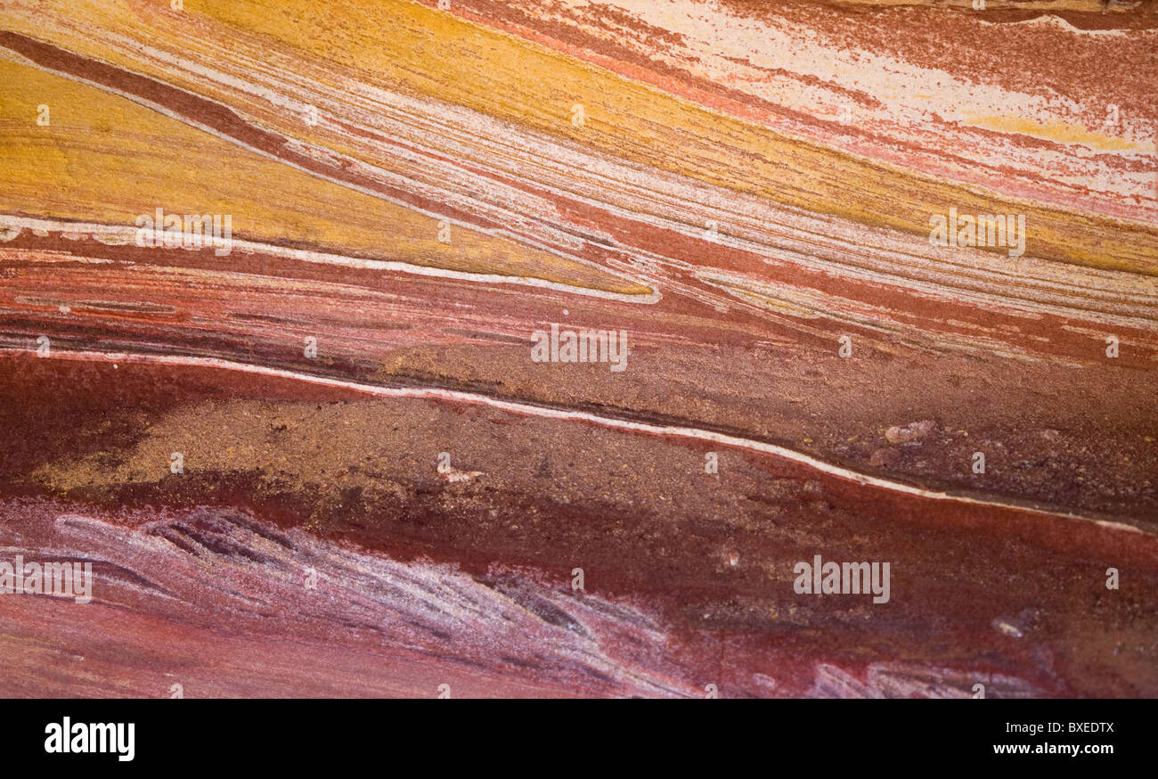 Banded sandstone rock in shades of red yellow and white reflecting different mineral content of constituent sands - Stock Image