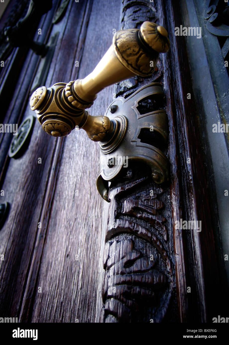 ornamental brass door handle on weathered old oak door Vienna Austria - Stock Image