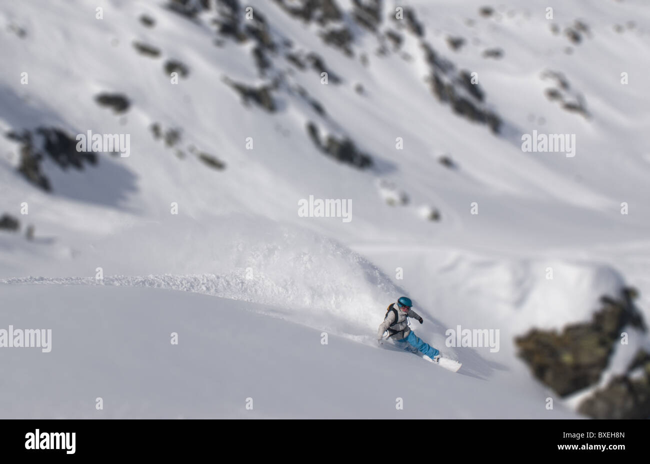 A lone snowboarder making a turn on a wide, empty snowfield in Zillertall, Austria - Stock Image