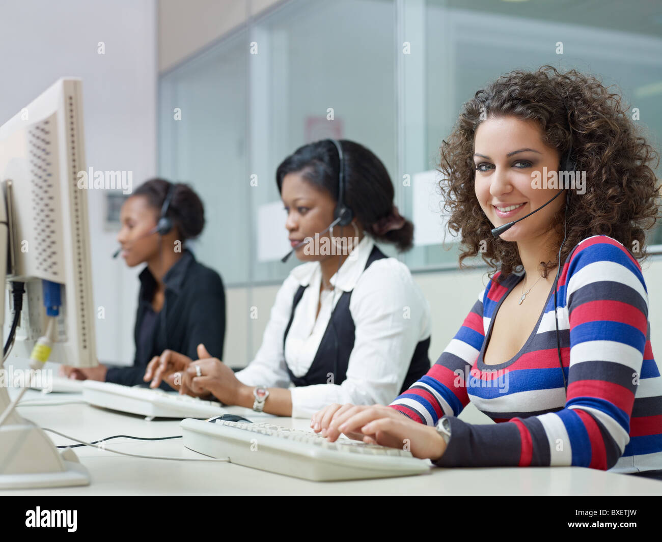 multiethnic group of female customer service representatives talking on the phone, with woman looking at camera. Stock Photo