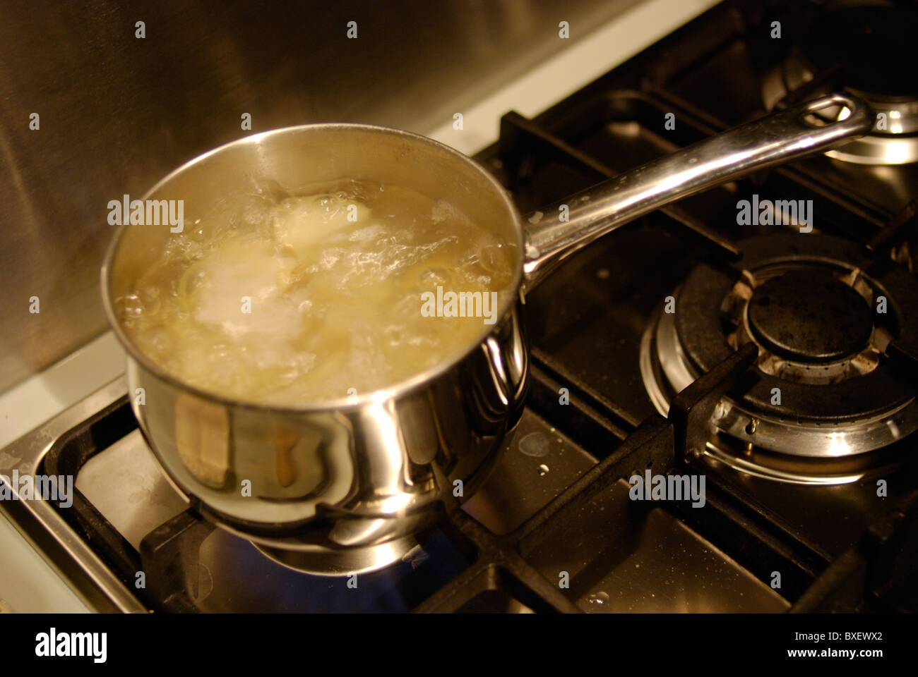 Potatoes simmering in a pan of boiling water on a gas hob. - Stock Image