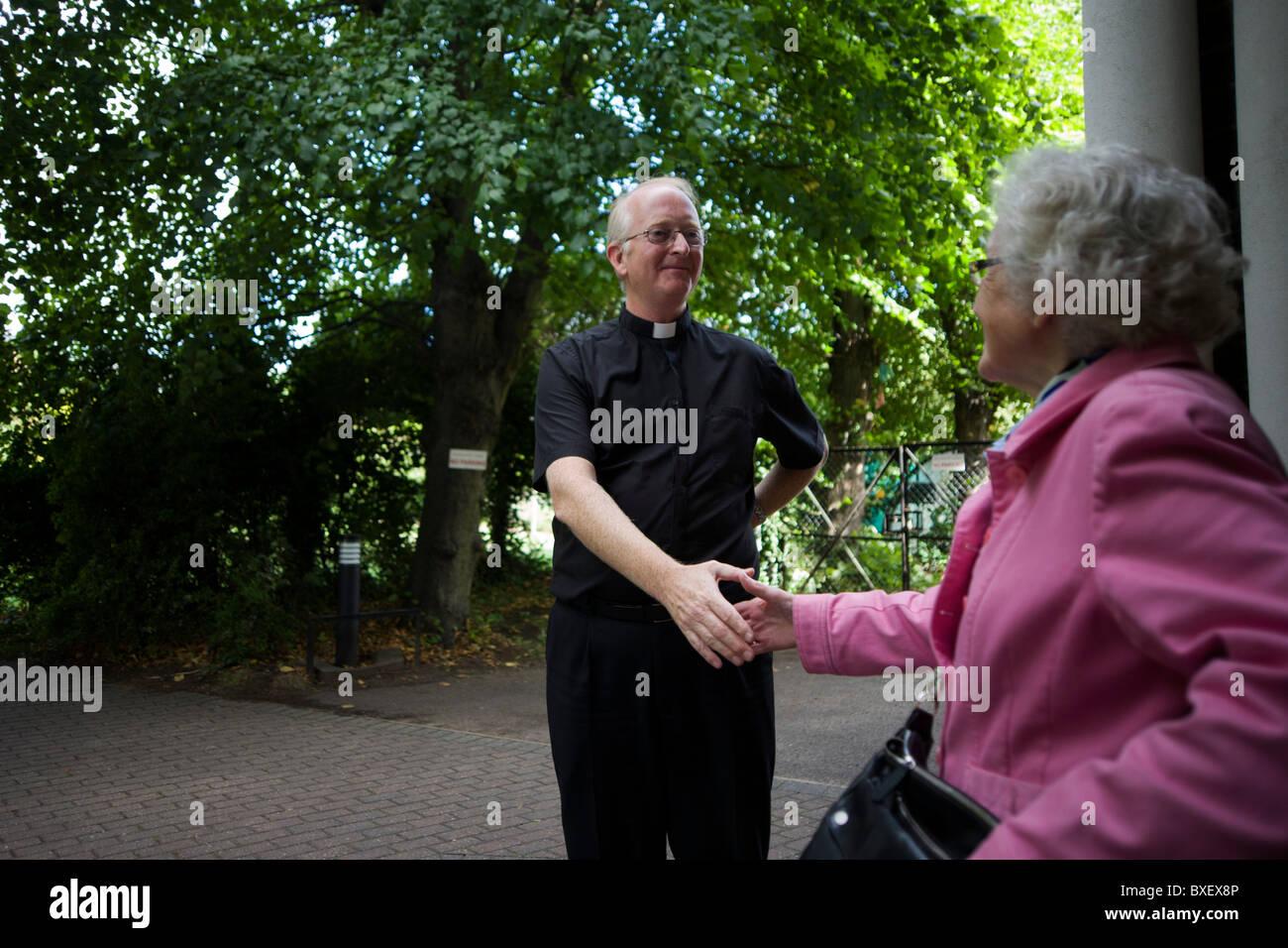 Catholic priest bids goodbye to parishioner after morning Mass at St. Lawrence's Catholic church in Feltham, - Stock Image