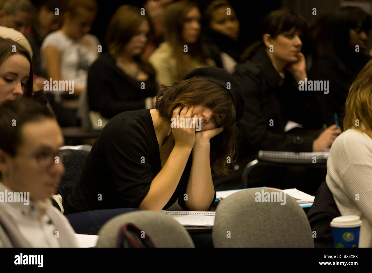 Tired girl student sleeps through lecture in Henry Thomas lecture theatre at London Metropolitan University. - Stock Image