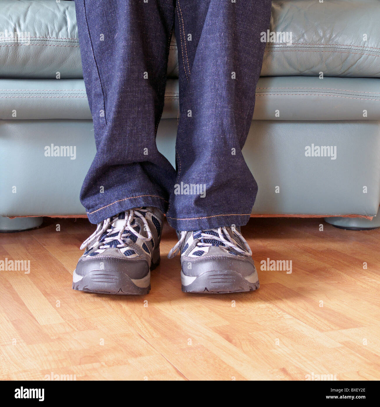 Man wearing a pair of Trainers ( Sneakers ) whilst sitting down in a leather armchair, UK MODEL RELEASED Stock Photo