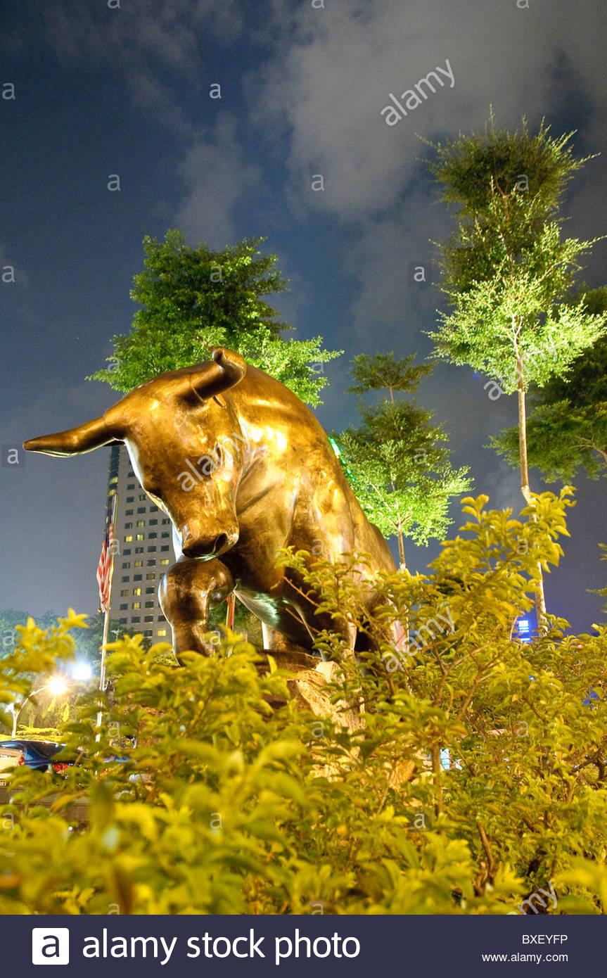 Illuminated bronze sculpture of a bull at night, Kuala Lumpur, Malaysia, Southeast Asia, Asia - Stock Image