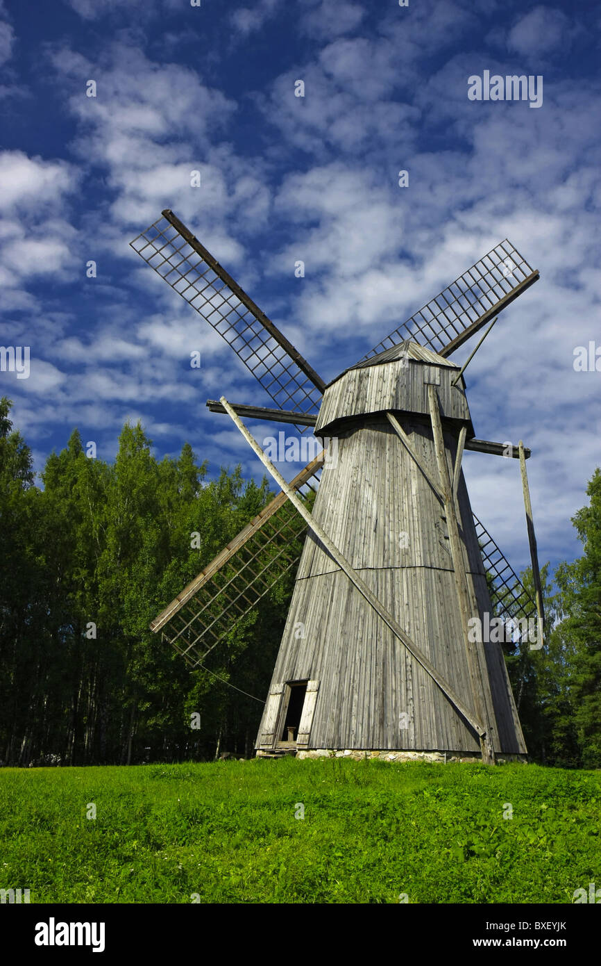 A vertical image of a large old windmill made of wood, typical for Northern Europe. - Stock Image