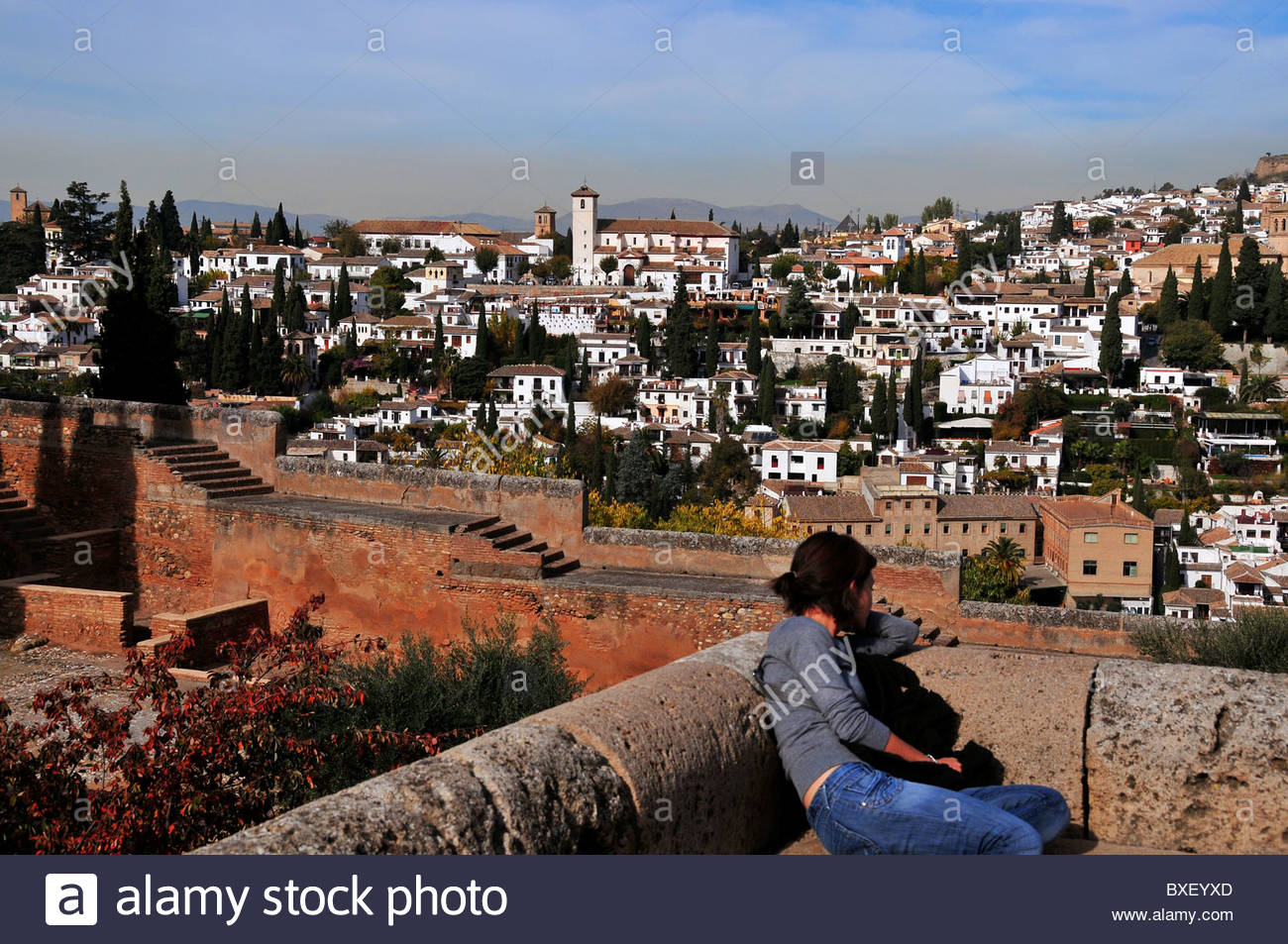 A young woman sits on the walls of the Alhambra and looks at the old quarter of El Albaicin on the hill opposite. - Stock Image