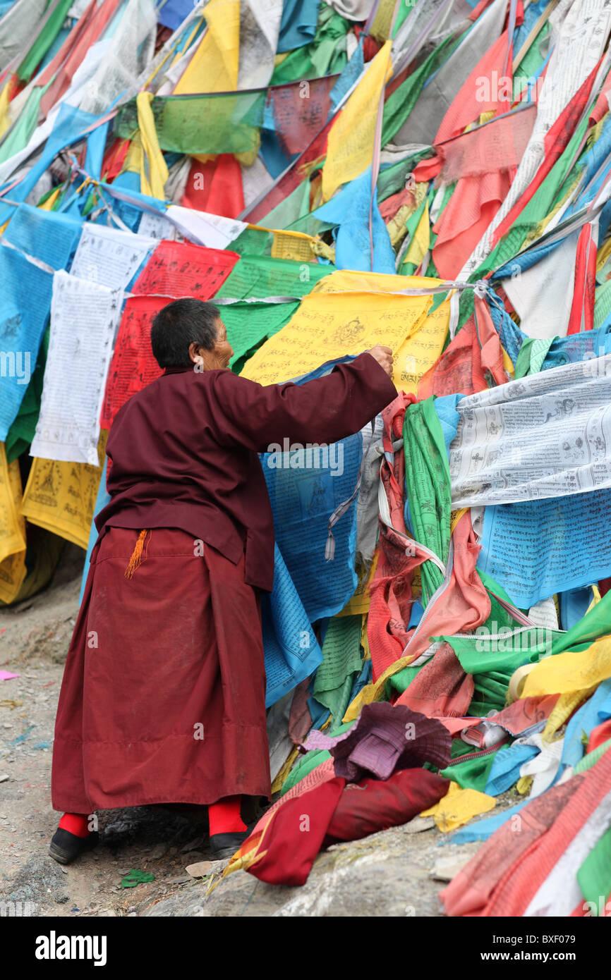 Monk with prayer flags on outer pilgrim path or Lingkhor around Iron Mountain in Lhasa, Tibet (Tibet Autonomous Stock Photo