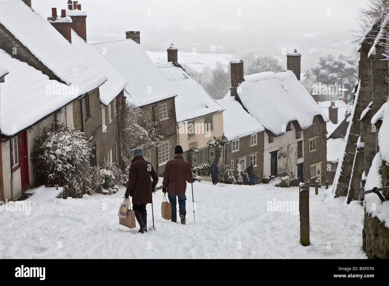 Two people carefully making their way down Gold Hill in Dorset in the snow on a December morning. People not identifiable. - Stock Image