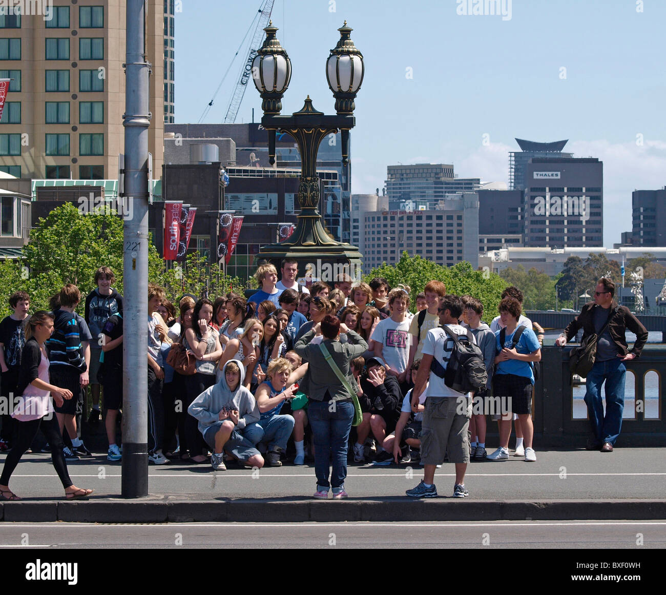 GROUP POSING FOR PHOTOGRAPH ON BRIDGE OVER RIVER YARRA MELBOURNE VICTORIA AUSTRALIA - Stock Image