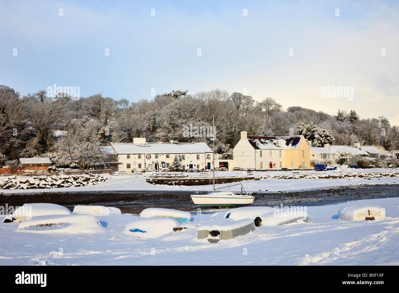 Village snow scene with upturned boats on coast in AONB in winter December 2010. Red Wharf Bay (Traeth Coch) Isle - Stock Image