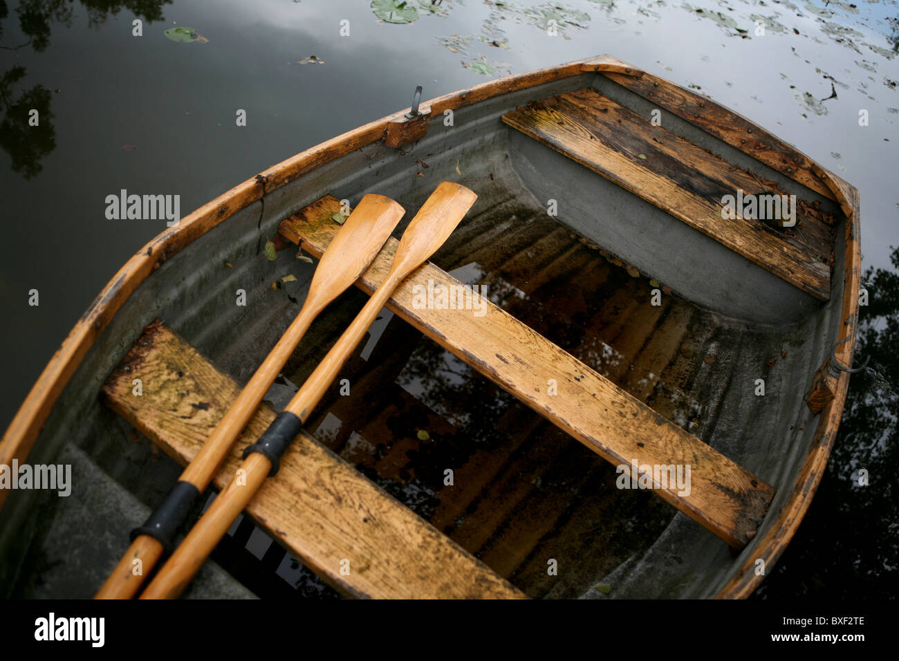 An old weather-beaten wooden row boat with oars, view from above. - Stock Image