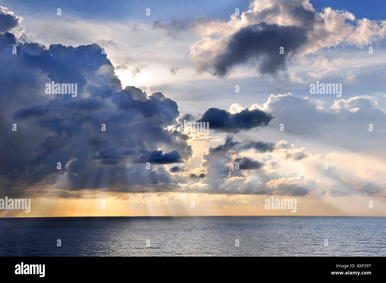Caribbean sunset at sea with sun rays and clouds - Stock Image