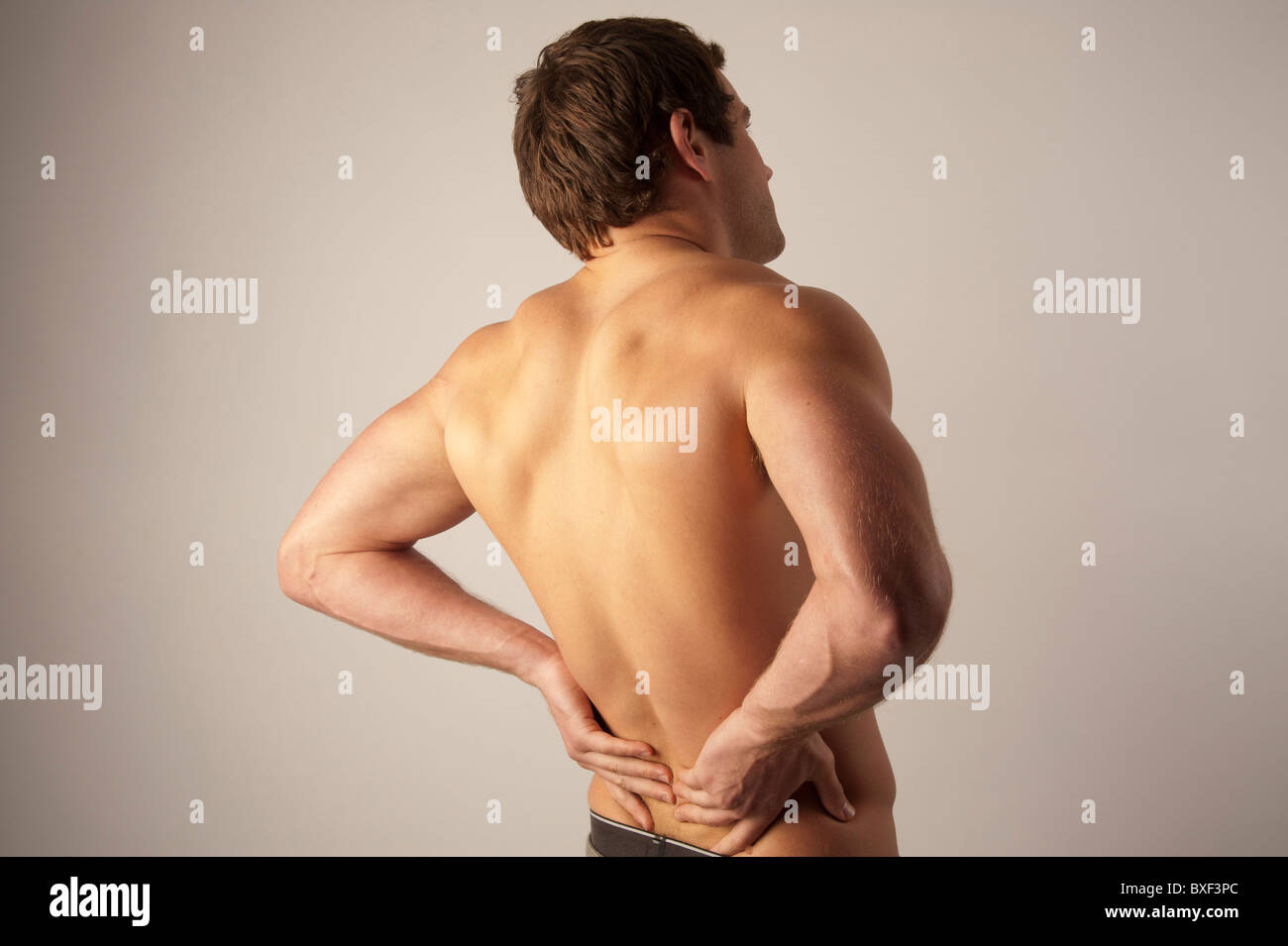 Rear view of a white caucasian male man rubbing his back, suffering from lower back ache pain, - Stock Image