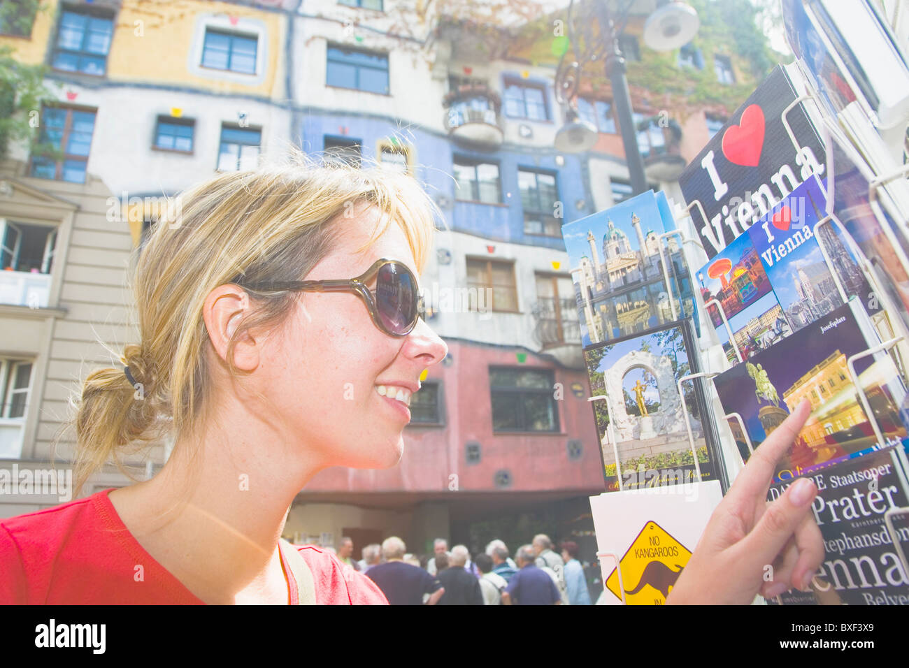 Woman looking at postcards in Vienna with the famous hundertwasserhaus in the background - Stock Image