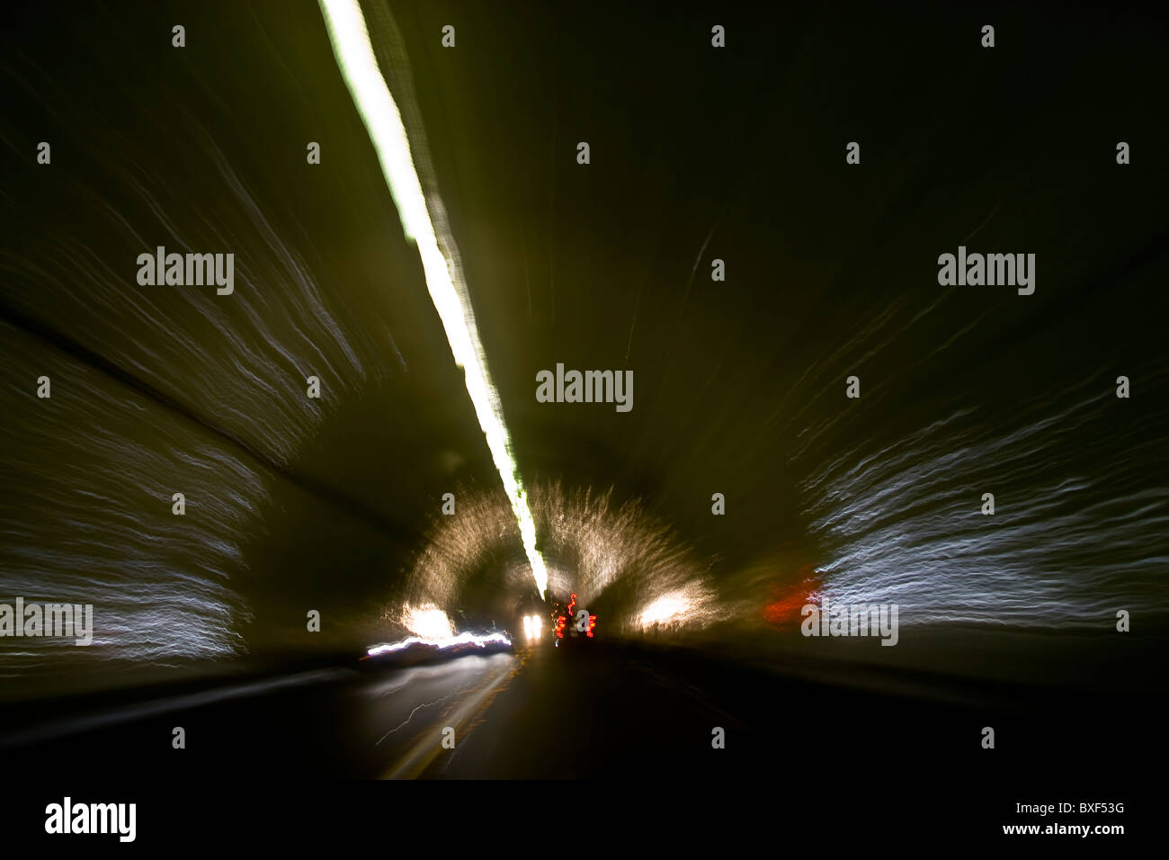 Car speeding through a tunnel with head lights and tail lights reflecting off  dome and sides of the tunnel Stock Photo