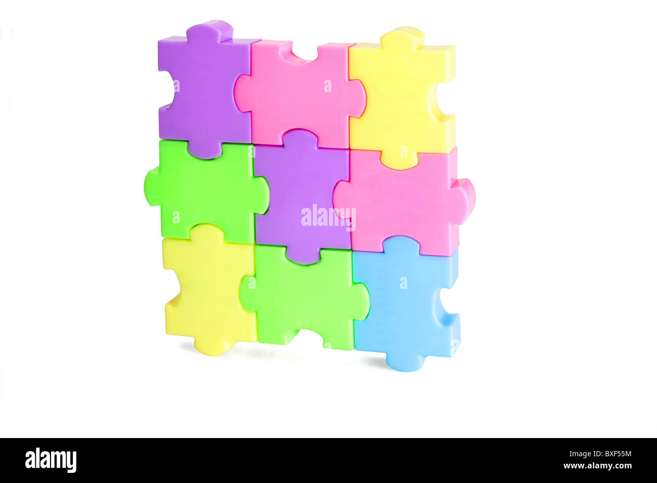 Colorful plastic jigsaw puzzle blocks on white background - Stock Image