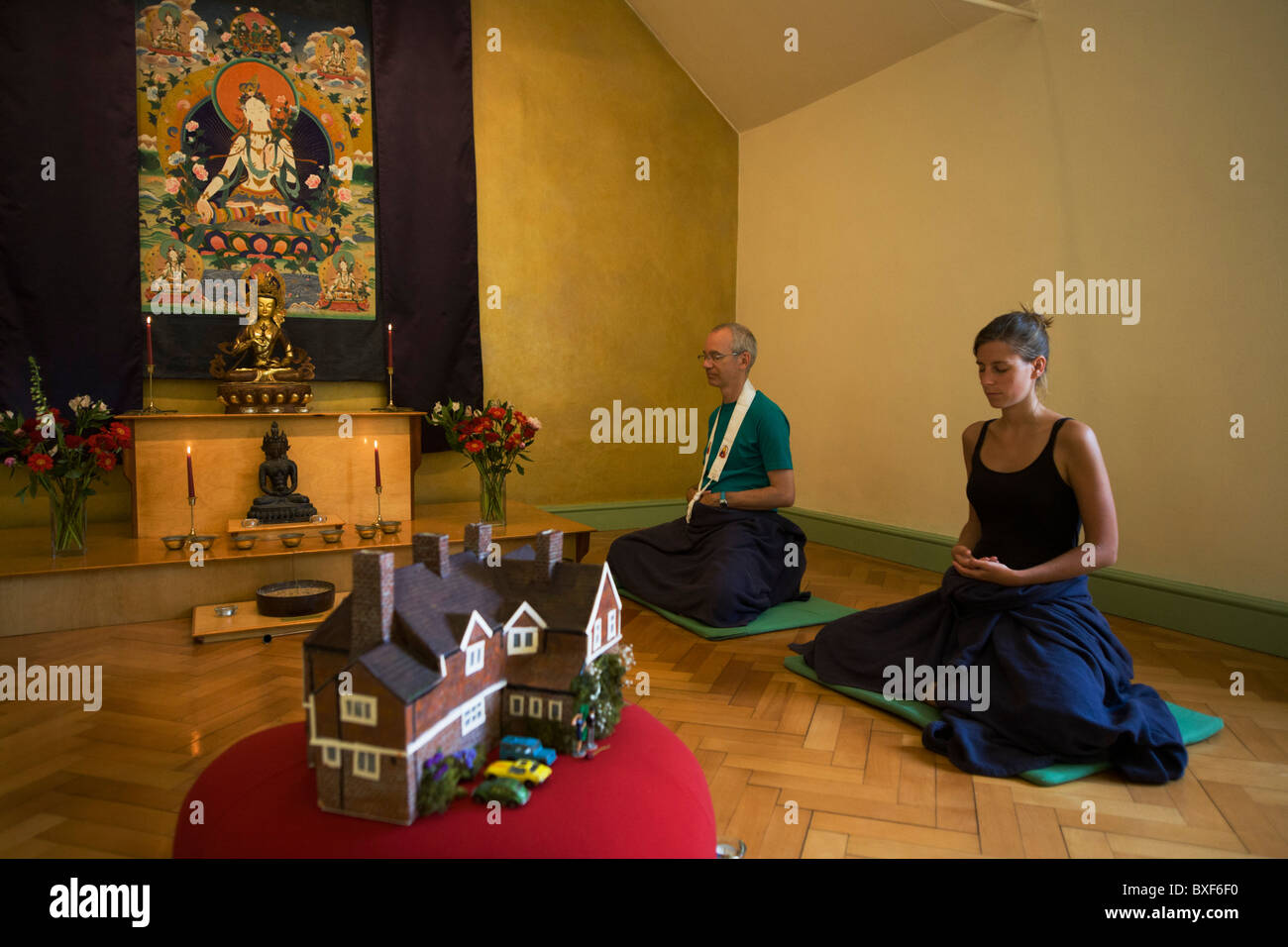 Buddhists meditate in silence for 30 minutes in their Shrine Room at the Rivendell Buddhist Retreat Centre, England. - Stock Image