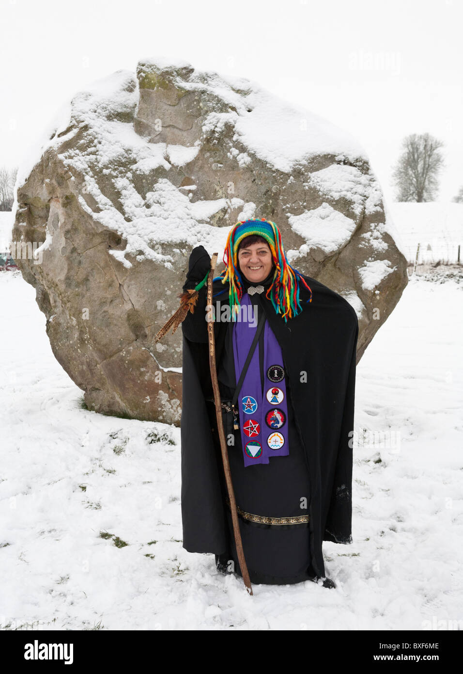A druid celebrating the Winter Solstice in the snow at Avebury stone circle, Wiltshire, UK - Stock Image